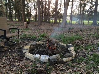 Large campfire pit with lots of firewood and seating.